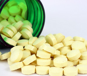 Yellow pills in a green vial