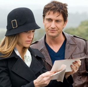 A woman stands next to a man and reads a letter