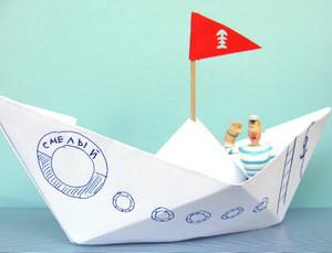Белый бумажный кораблик с красным флагом