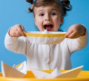 Девочка сделала кораблик из бумаги