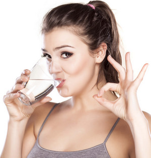 The girl drinks clear water from a glass.