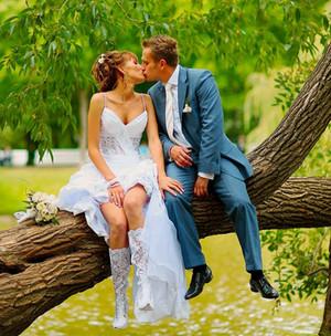 Молодожены фотографируются сидя на ветке дерева