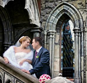 Жених и невеста стоят на лестнице замка