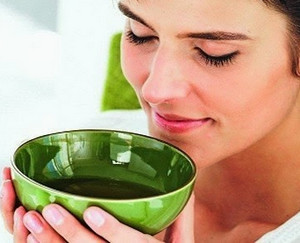 A girl holds a cup with a decoction of herbs