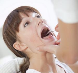 Doctor examines the patient's throat