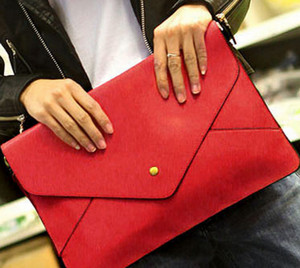 Red clutch envelope in female hands