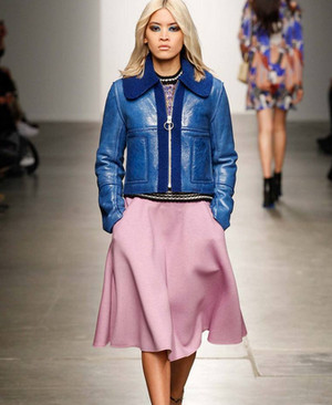 Model in a pink leather skirt and blue jacket