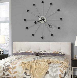 Clock with arrows above the bed