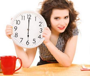 Девушка держит в руках круглые часы