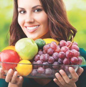 Девушка с фруктами в стеклянной тарелке