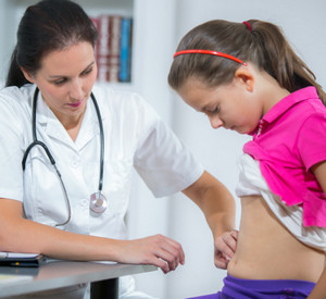 Doctor examines the belly of a girl