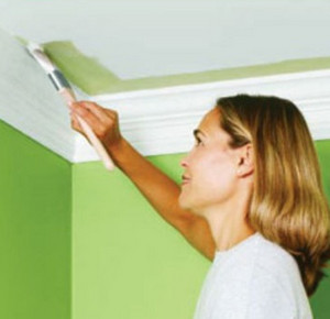 Woman paints the ceiling in the bathroom in green