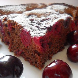 A piece of chocolate cake with cherry