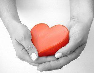 A girl holds a heart figure