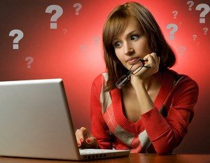 Girl sitting near the laptop and question marks on the background