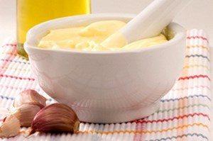 Mayonnaise in a saucepan, near garlic