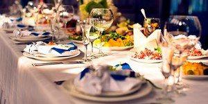 Праздничный стол с бокалами, тарелками и блюдами