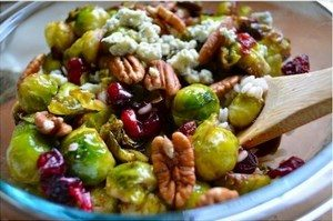 Brussels sprouts salad with nuts in a bowl with a wooden spoon