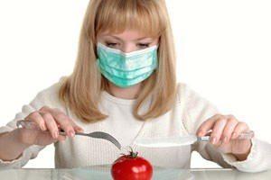 Girl in mask eats tomato