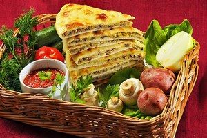 Slices with Ossetian cake and a number of vegetables and greens