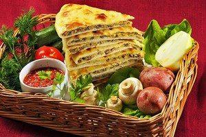 Кусочки с осетинским пирогом и рядом овощи и зелень