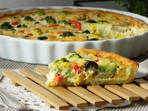 A slice of quiche with vegetables