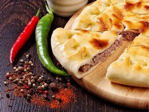 Пирог с начинкой, рядом лежит перец