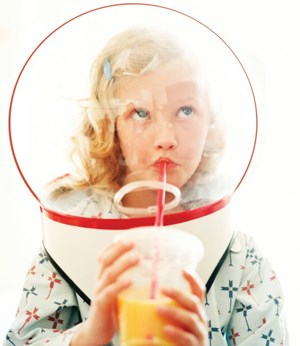 A child in a spacesuit drinks juice