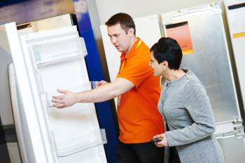 the sales assistant shows the refrigerator